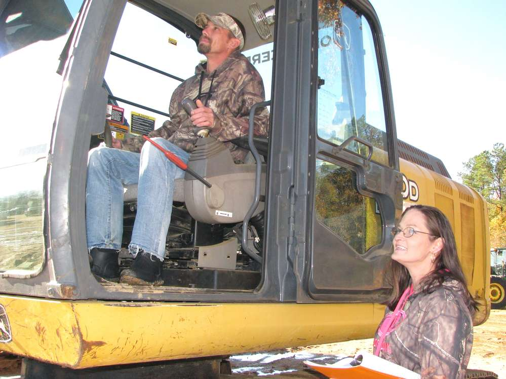Jesse Touchstone (L) and Terri Danne, both of Danne Dirt, Fairhope, Ala., check out this Deere excavator.