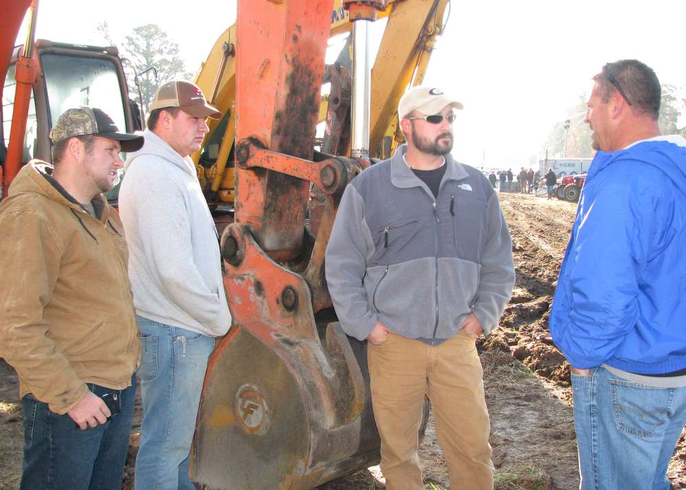(L-R): Jason White, Matthew Harman and Sam Harman, all of Harman Turf Farms, Franklin, Ga., and Jamie Perry, independent contractor based in Carrollton, Ga., discuss the machines available at the sale.