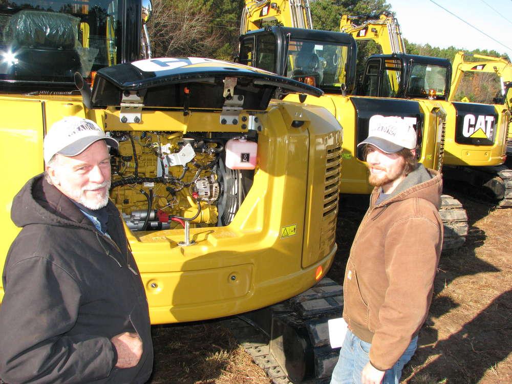 Jerry (L) and Logan Turner, both of Dog River Grading, Carrollton, Ga., look over a trio of new 2016 Cat 308e2 CR mini-excavators.