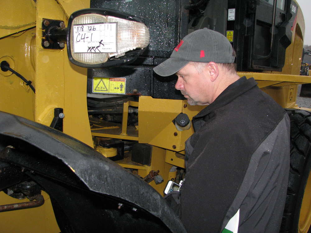 Steve Nethery of Artec Tractor & Equipment, Nauvoo, Ala., completes an inspection of the center articulation point of a Cat wheel loader.