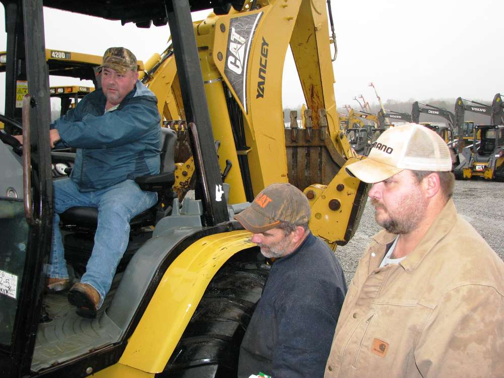 (L-R): Brian Yancey, Tommy Ward and Joey Vaughn, all of Contour Grading & Pipe, Bold Springs, Ga., check out the Cat backhoe loaders about to go on the block.