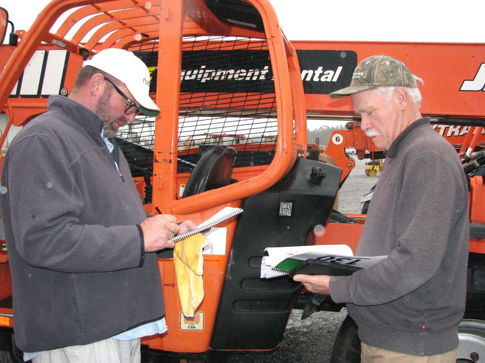 Mike (L) and Fred Miles, both of Mi-Com, Whitesburg, Ga., jot down a few final notes before bidding on machines.