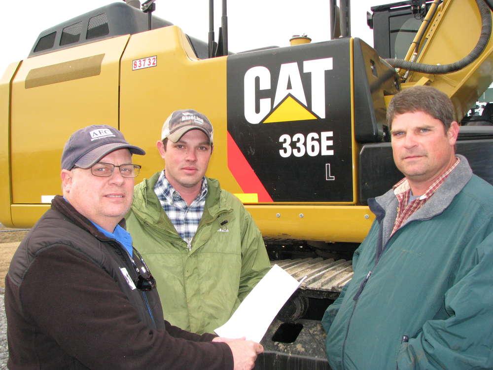 (L-R): William Steele, Brandon Dean and Justin Hastings, all of AEC Site Solutions, Huntsville, Ala., consider this 336EL excavator.