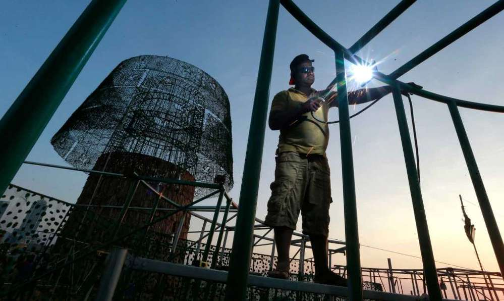 A Sri Lankan port worker welds steel frames to assemble an enormous, artificial Christmas tree on a popular beachside promenade in Colombo, Sri Lanka. Hundreds of Sri Lanka's port workers and volunteers are struggling to put up the towering Christmas tree in time for the holidays. The majority-Buddhist nation is aiming to beat the world record for the tallest, artificial Christmas tree as a show of multicultural respect.