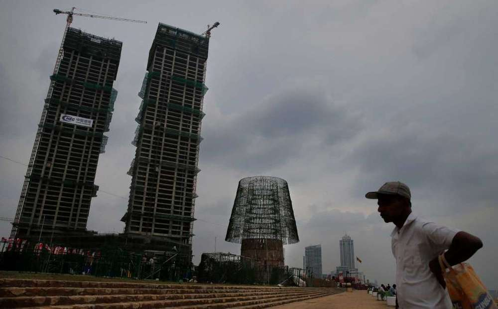 A Sri Lankan man stands near the construction site of an enormous, artificial Christmas tree, center, being built on a popular beachside promenade in Colombo, Sri Lanka. Hundreds of Sri Lanka's port workers and volunteers are struggling to put up the towering Christmas tree in time for the holidays. The majority-Buddhist nation is aiming to beat the world record for the tallest, artificial Christmas tree as a show of multicultural respect.