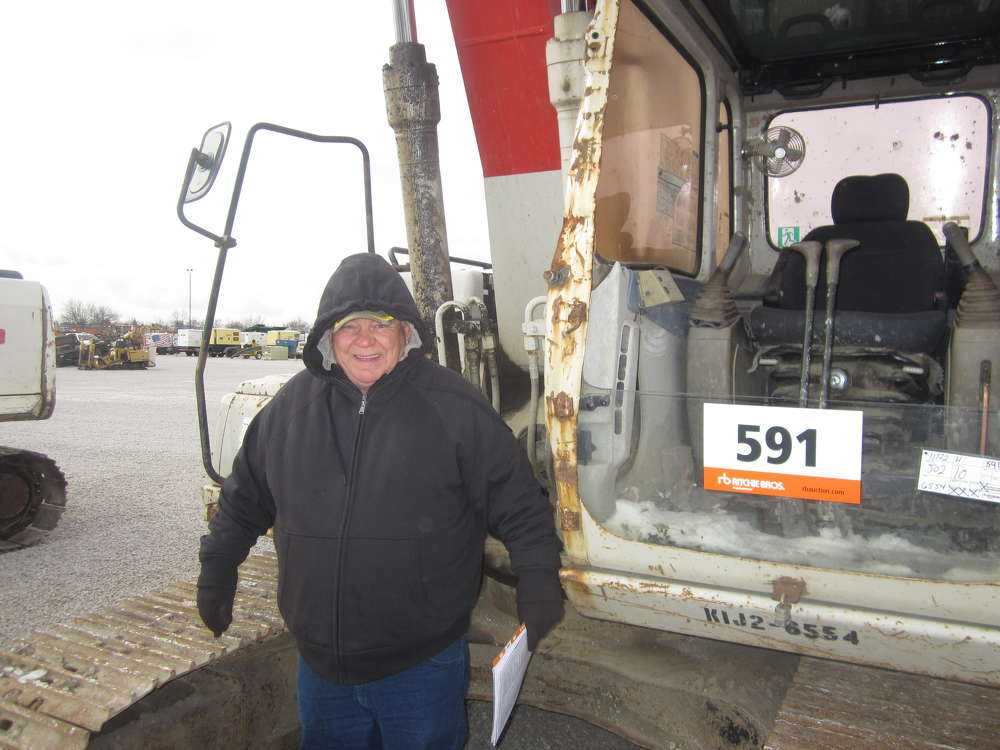 Henry Bennett of Beecher City Equipment looks over the excavators at the Ritchie Bros. auction.