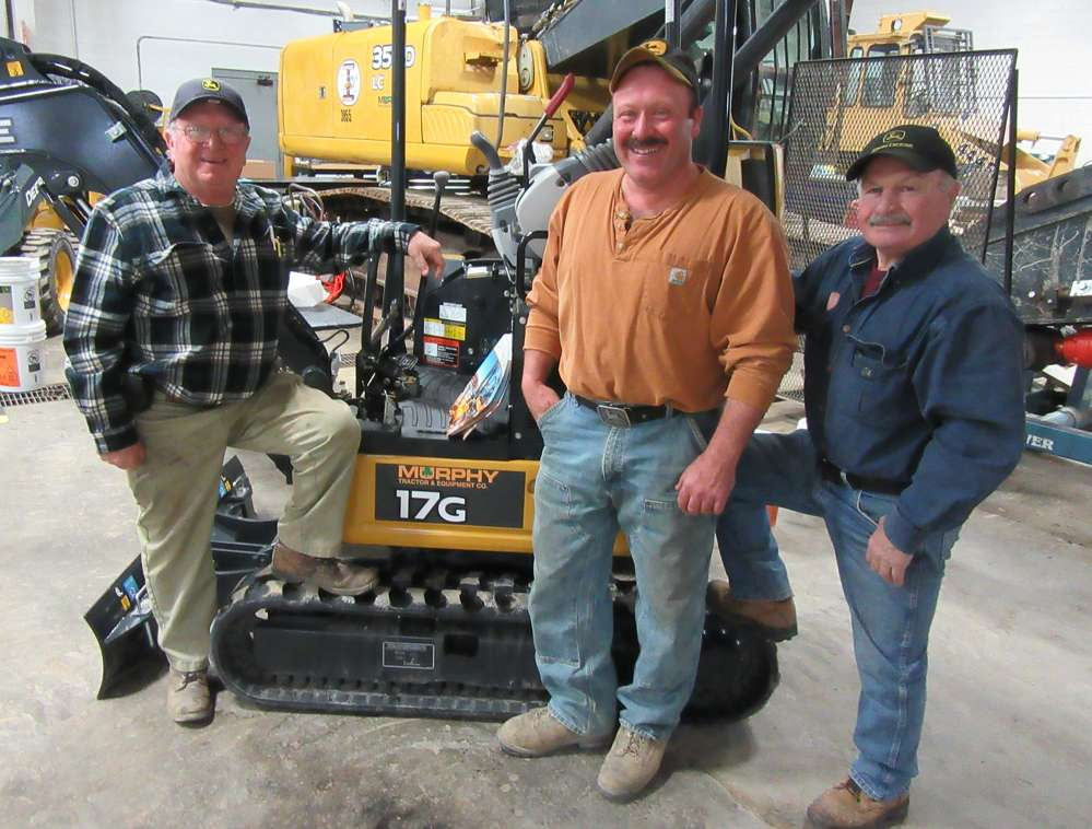 (L-R): John Croft and his son, Charlie, and brother, Rich, all of John Croft and Son Excavating, admire this John Deere 17G mini-excavator on display at the Brunswick branch.