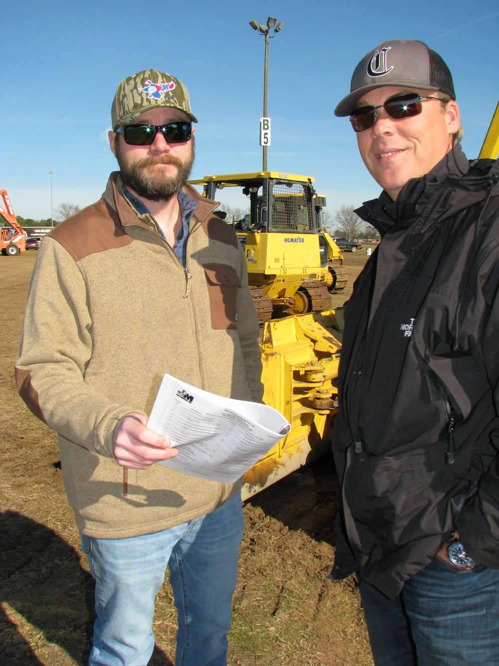 Clayton Porter (L) and Josh Hancock, both of Porter Equipment Company, Perry, Ga., talk about the machines they plan to bid on.