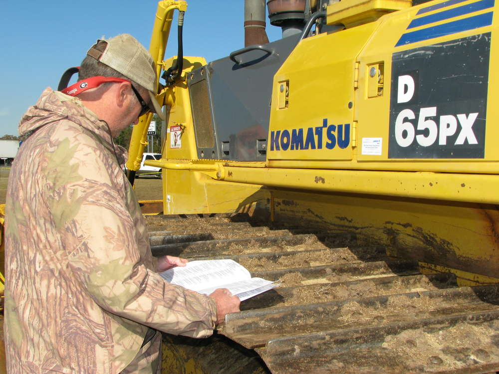 Andy Sparrow, independent contractor, Unadilla, Ga., studies his notes before the auction.