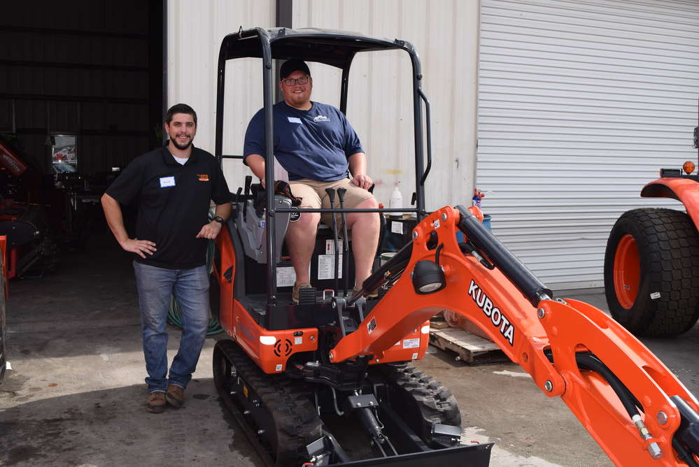 Kevin Edling (L), sales representative of Florida Coast Equipment, and Aaron Tull of Tall Oaks, Naples, Fla., test this new Kubota mini-excavator KX 018-4