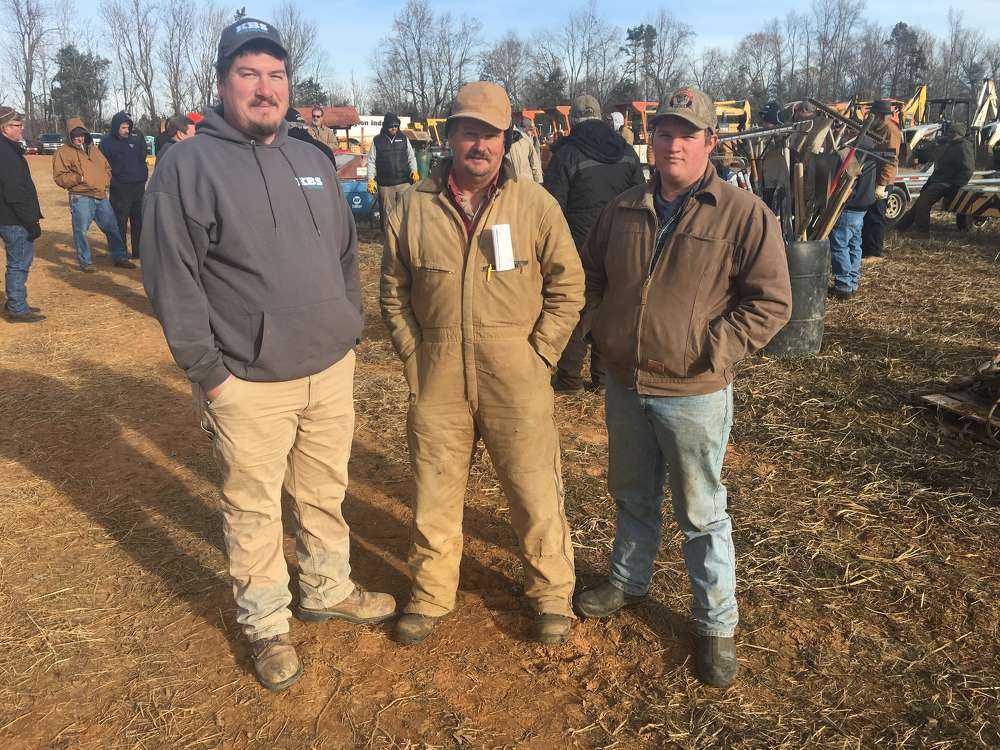 (L-R): Kory Strader of KBS Earthworks in Julian, N.C., and Frank and Nicholas Strader, both of Strader Farms in Julian, N.C., look at the backhoe loaders.