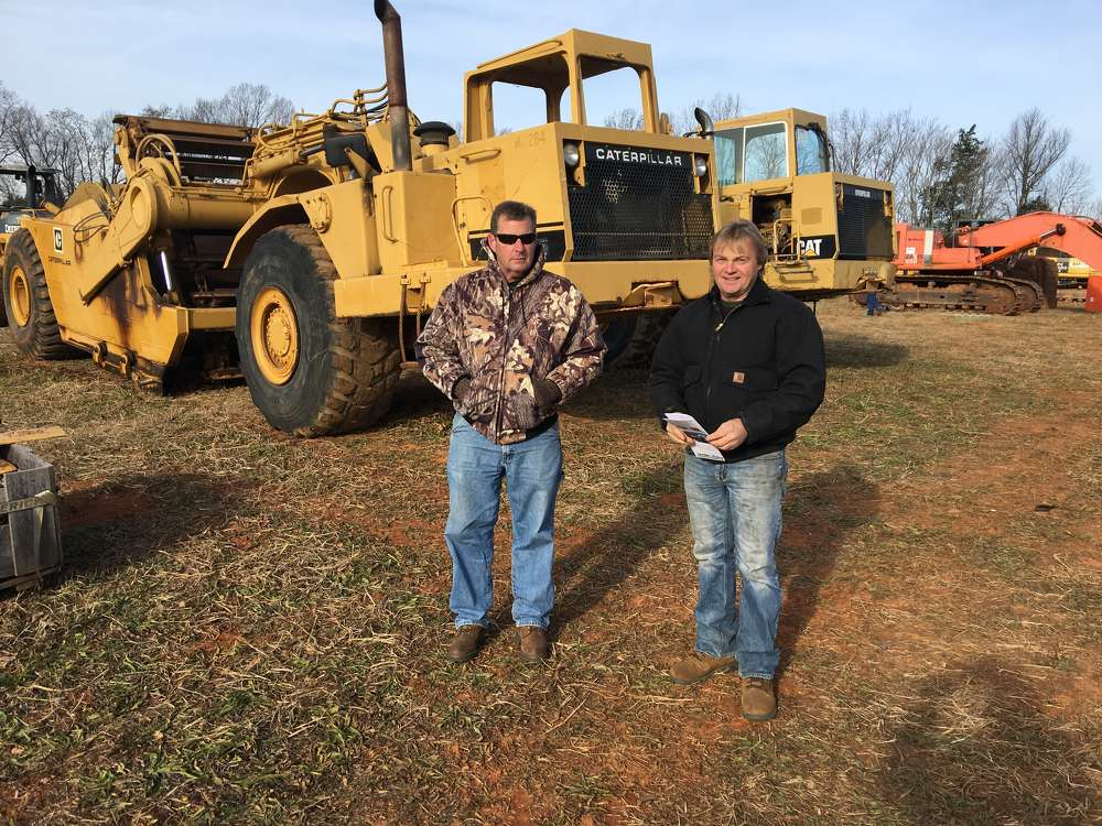 Keith Garner (L) of Garner Contracting in Robbins, N.C., and Marty Maness, Maness Backhoe Service, in Robbins, N.C., take a look at the Cat scrapers.