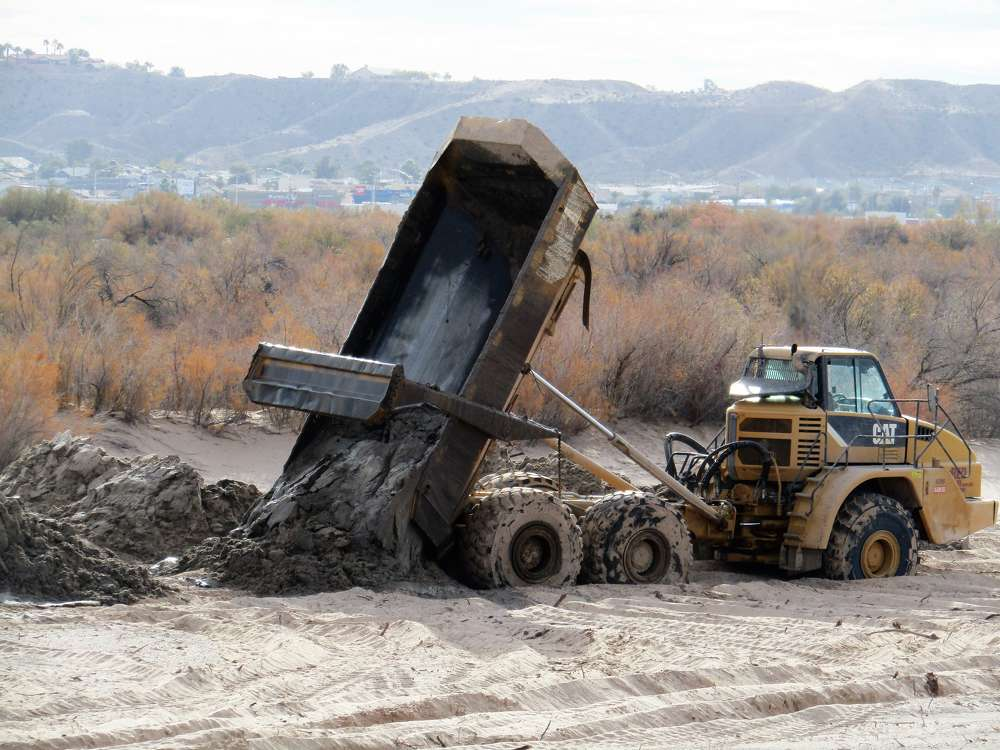 The Cat hauler dumps dredged material at the fill site.