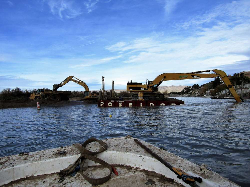 A Cat 345CL excavator with an extended arm dredges the marina.