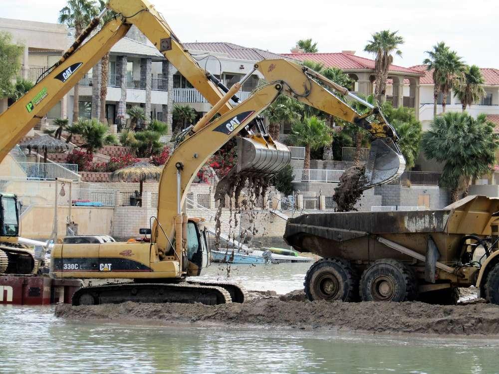 Cat excavators load the Cat hauler with river mud.