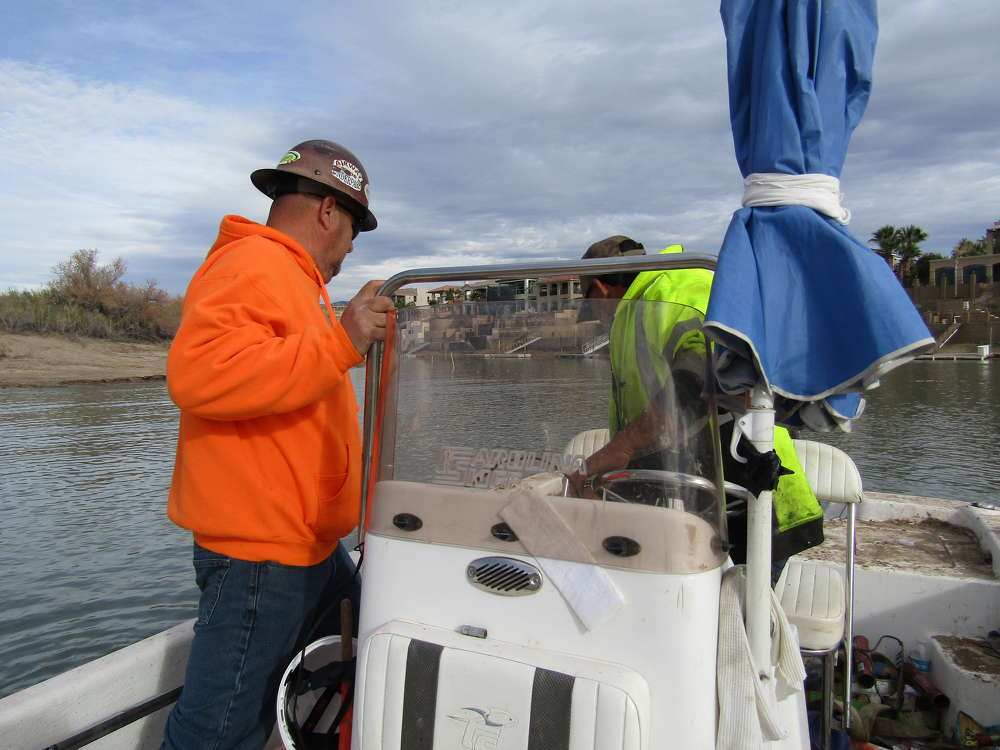 Alberto Mendoza (L) and pilot need the boat for safety, transport, maintenance and to continuously check depths.