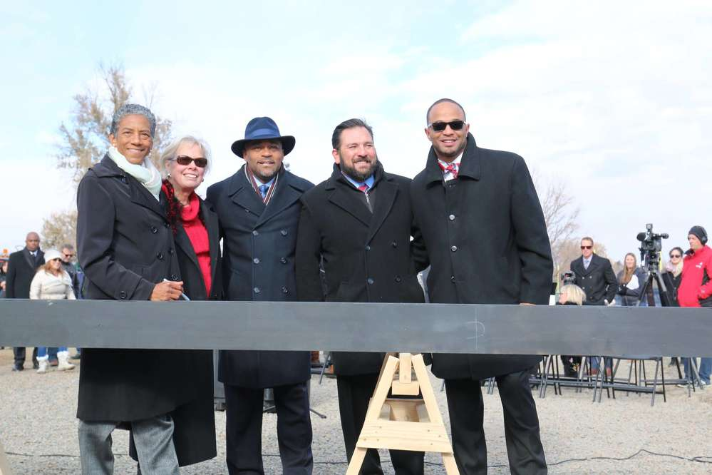 Denver Mayor Michael Hancock (C) and city officials, along with the construction and design team members, signed the ceremonial beam before it was placed on top of the structure being constructed.