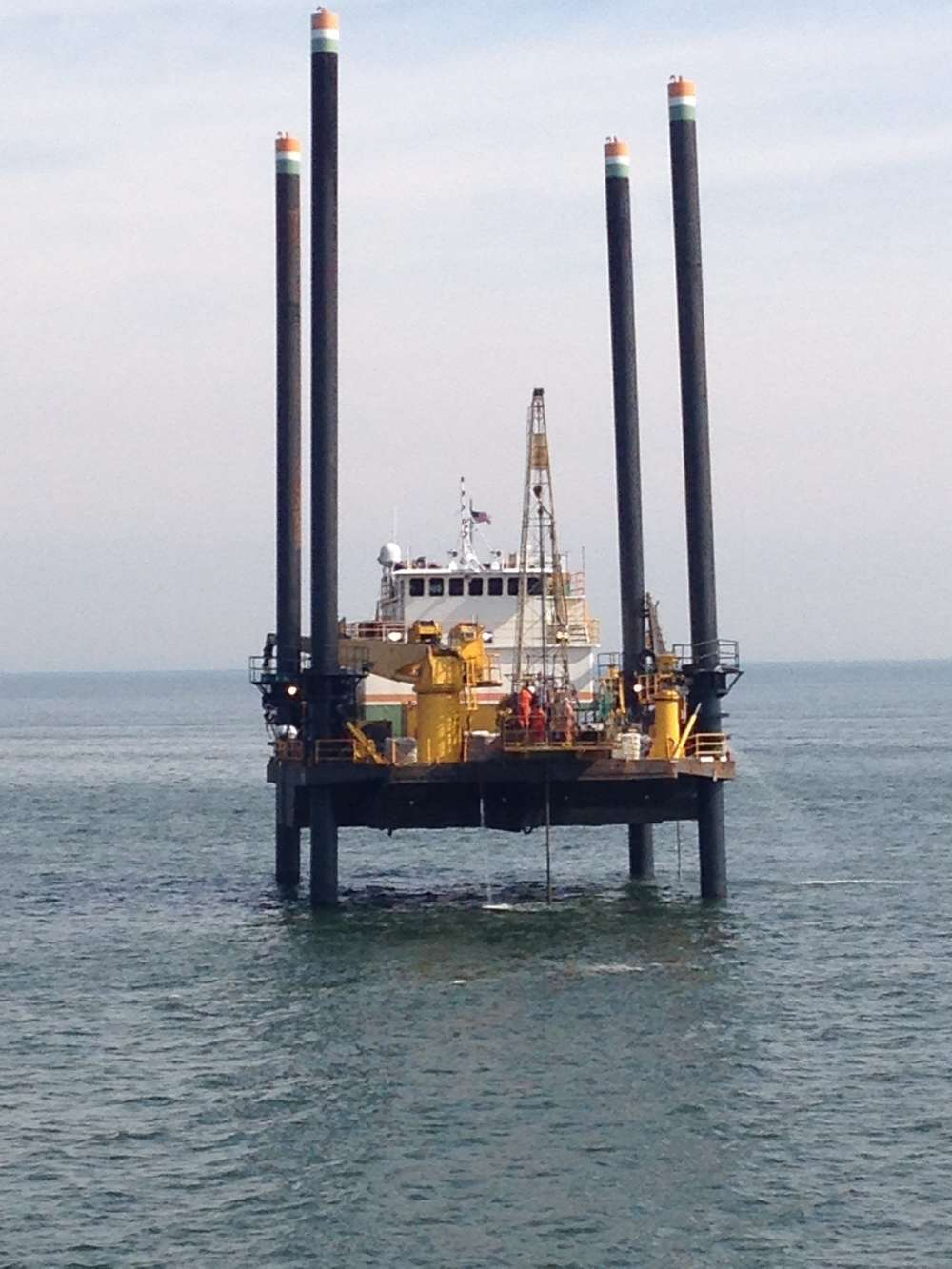 A jack-up barge takes borings of the channel.