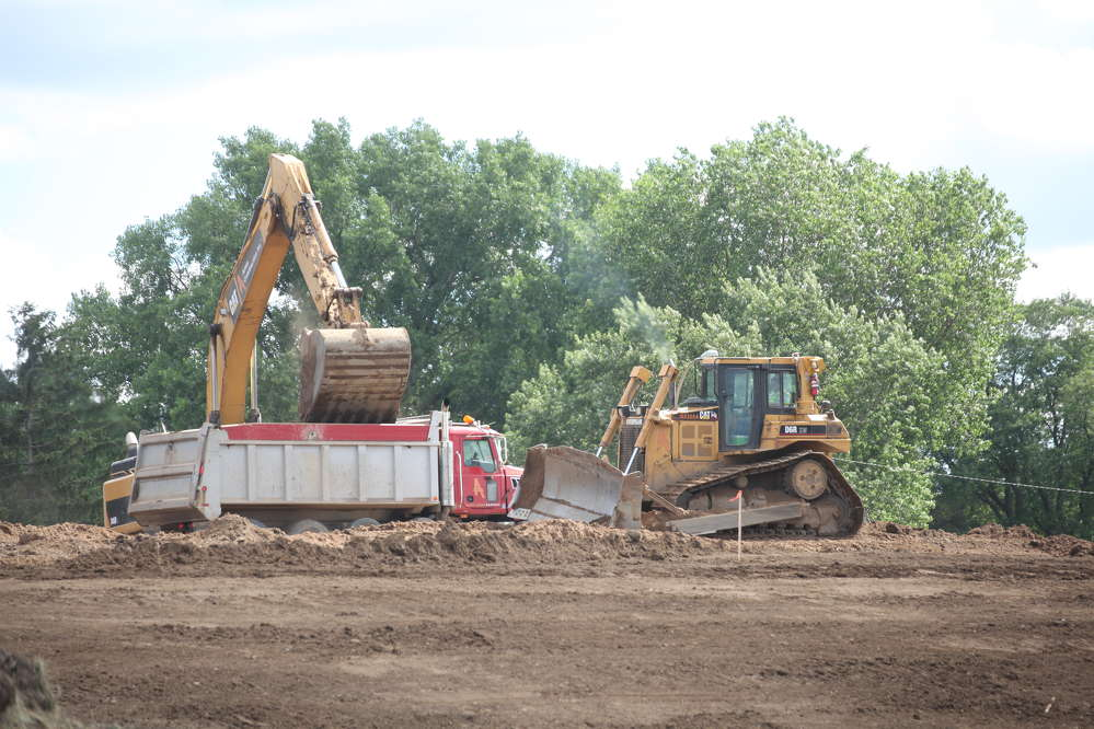 The operator of a Cat excavator and dozer work the ground at the site of the old TH 36 bridge.