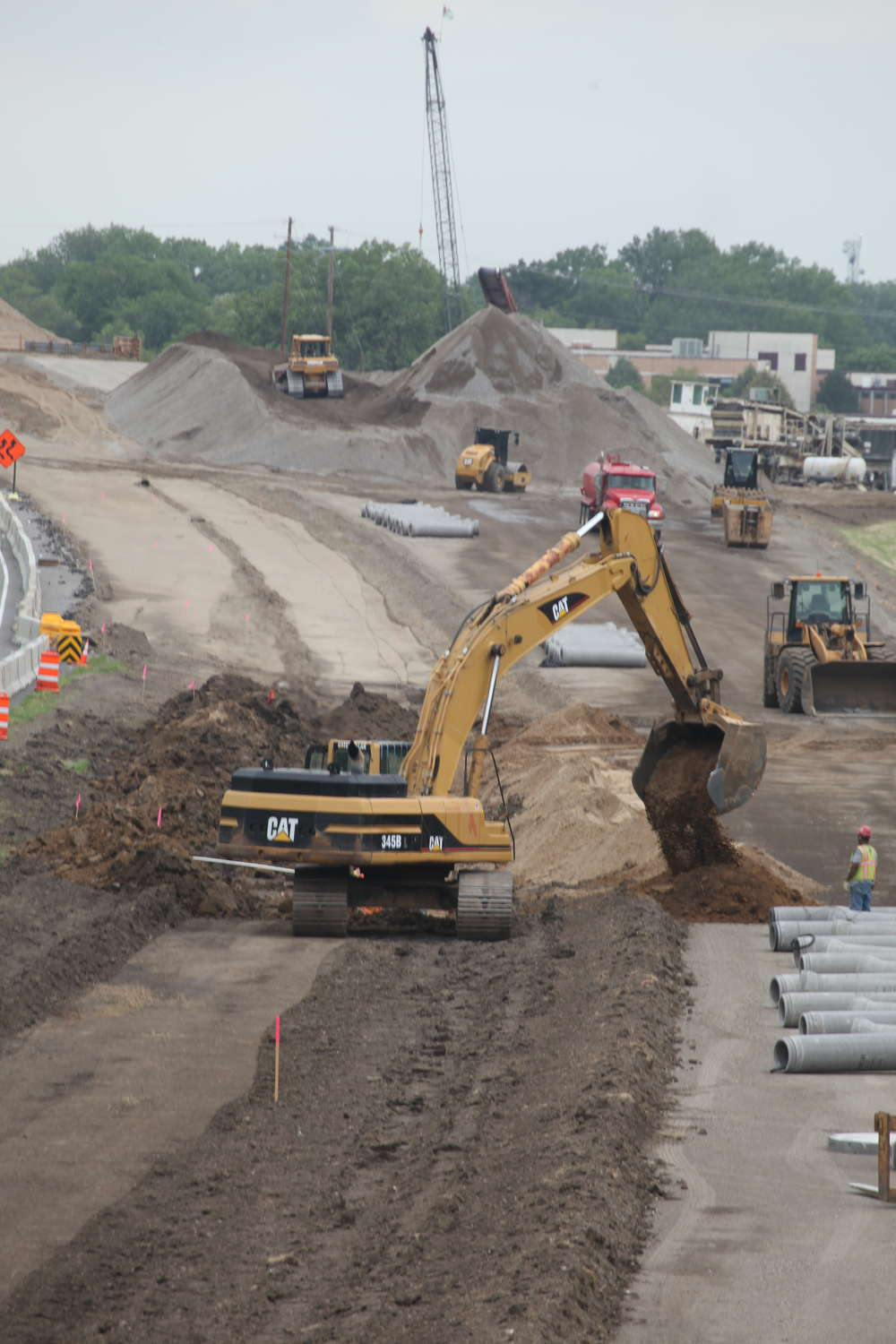 Crews work on a section of the new highway digging sewer, grading and pushing dirt.