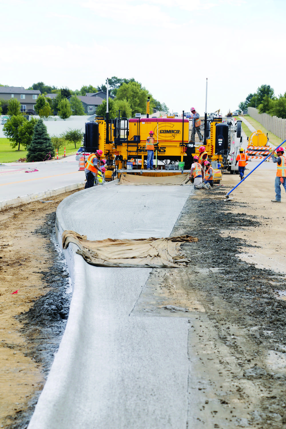 The GP3 slipforms a scab-on tapered slab with integral curb in traffic in urban conditions.