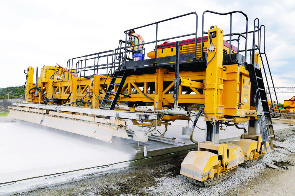 One pass texturing and curing is possible with the four-track T/C 5600. Covered sensors on the texture/cure machine follow the edge of the slab to steer it down the length of new interstate.