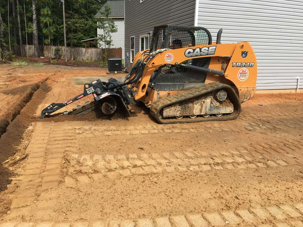 The operator of a Case TR320 compact track loader equipped with a Bradco trencher is digging the irrigation lines for a newly built home.