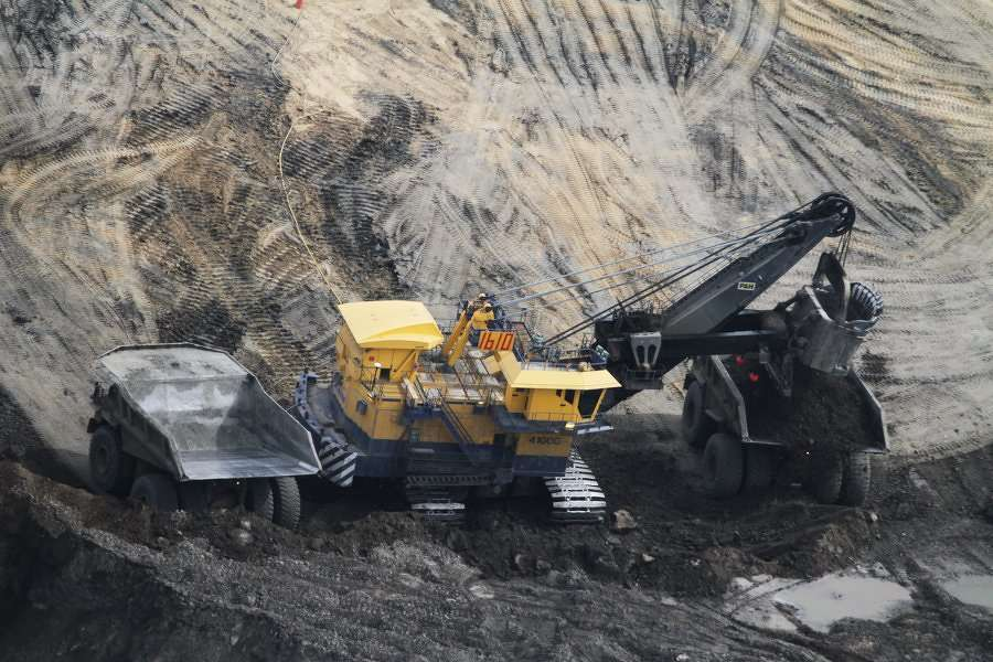 Robert Johnson — Business Insider. The excavator loads the giant dump trucks with the oil-rich sand.