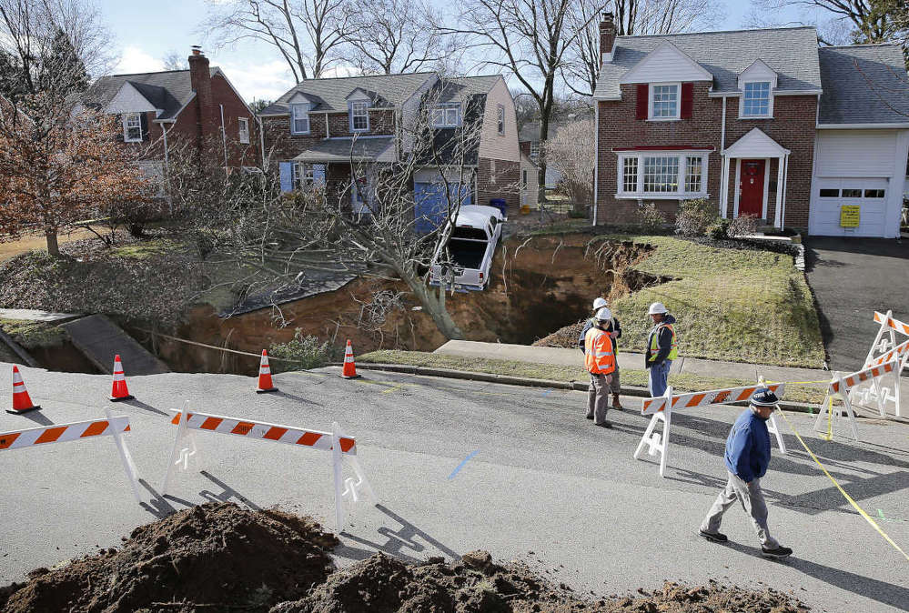 A pick-up truck hangs on the edge of a large sinkhole on the 700 block of Brooke Road in Glenside on Jan. 25, 2017.