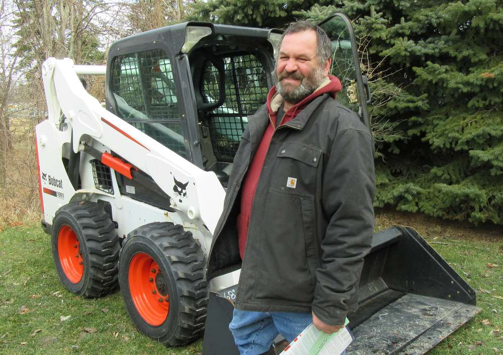 Dominic Bockmore of Bockmore Dairy Farms considers a bid on this Bobcat S530 skid steer loader.