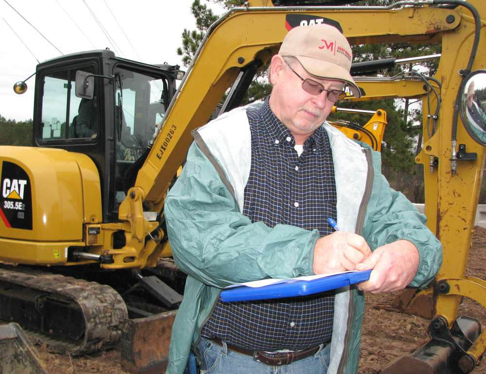 Billy Sibley, Sibley Equipment Company, Woodstock, Ala., takes a few notes on the equipment.