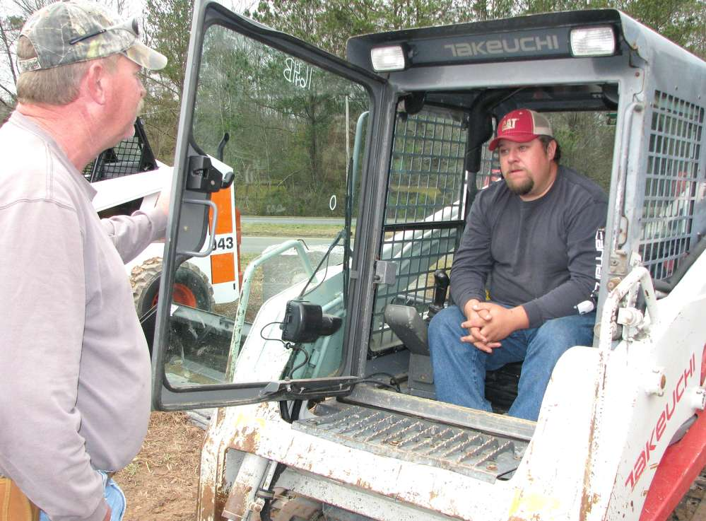 Craig (L) and Allen Hembree of C & A Grading, Franklin, Ga., consider this Takeuchi TL230 compact track loader.