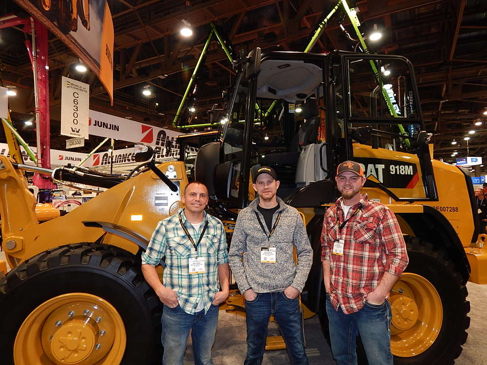 "At the Caterpillar booth with a Cat 918M wheel loader is the crew from Crow River Construction of New London, Minn. (L-R): Owner Kraig Hanson, Equipment Operator Jacob Bengson and Estimator Devon Lien. Hanson said that he buys his company's Cat equipment from Ziegler Cat in Bloomington, Minn. ""They offer great equipment, great parts and service,"" he said. ""We are really happy with our Cat Equipment and push it hard in the field."""