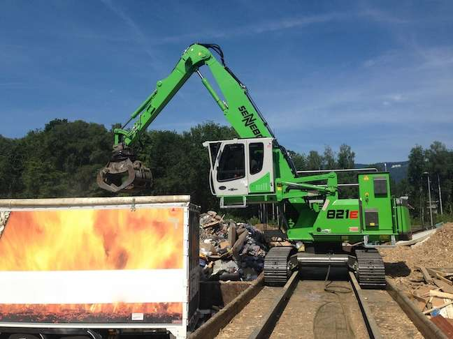 A trailing cable supplies electric current to the Sennebogen 821 as it moves along a ramp handling waste material at the Remo Recycling AG facility. The specially-designed industrial maXCab features bullet-proof armored