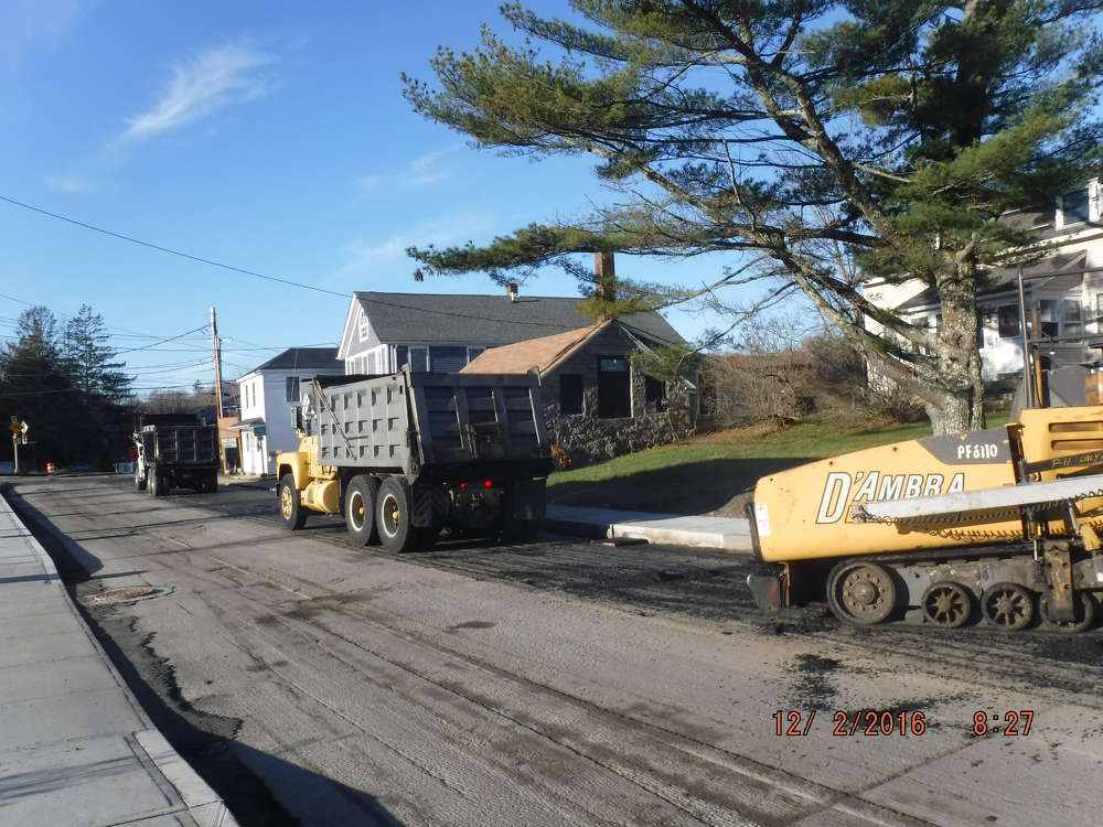 Equipment on the two-lane highway and sidewalks includes various loaders, backhoes, pavers, concrete trucks and sweepers.