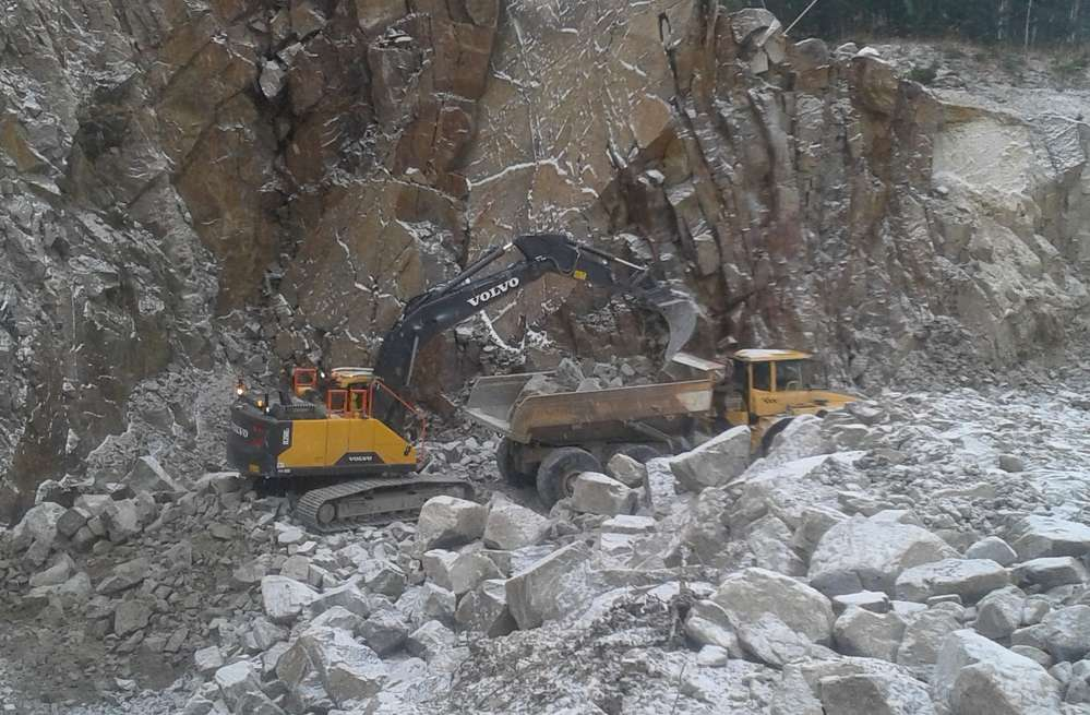 A Volvo EC220E excavator loads an A35D articulated hauler in the snow-covered quarry.