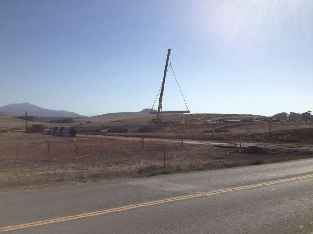 Workers lift prefabricated girder into place at the Arroyo Del Oso Bridge.
