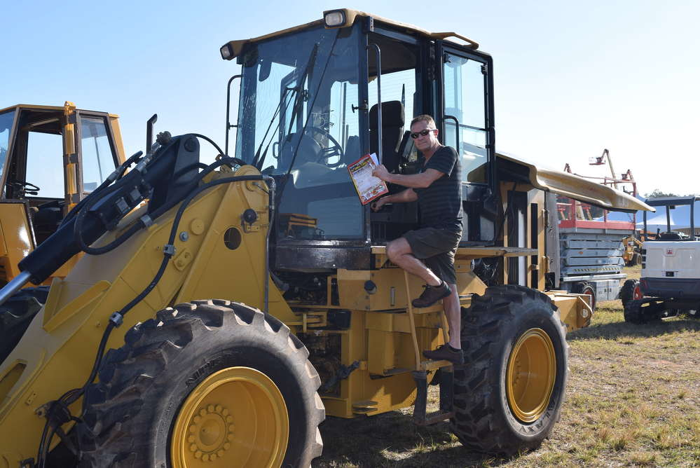 With a guide in his hand, Dean Bockenhauer of Midwest Equipment from St. Charles, Minn., gets ready to crank up this Caterpillar 924 G wheel loader before bidding on it.