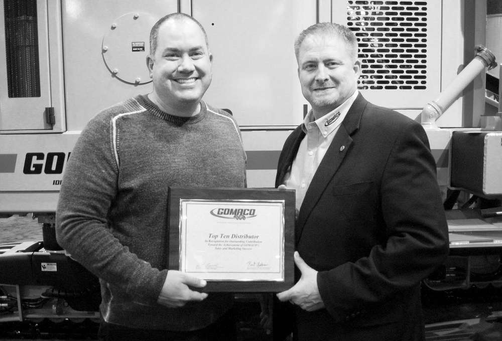 Andru Small (L), Terry Equipment Inc., accepts the Top Ten Distributor award from Kent Godbersen, GOMACO vice president of worldwide sales and marketing.