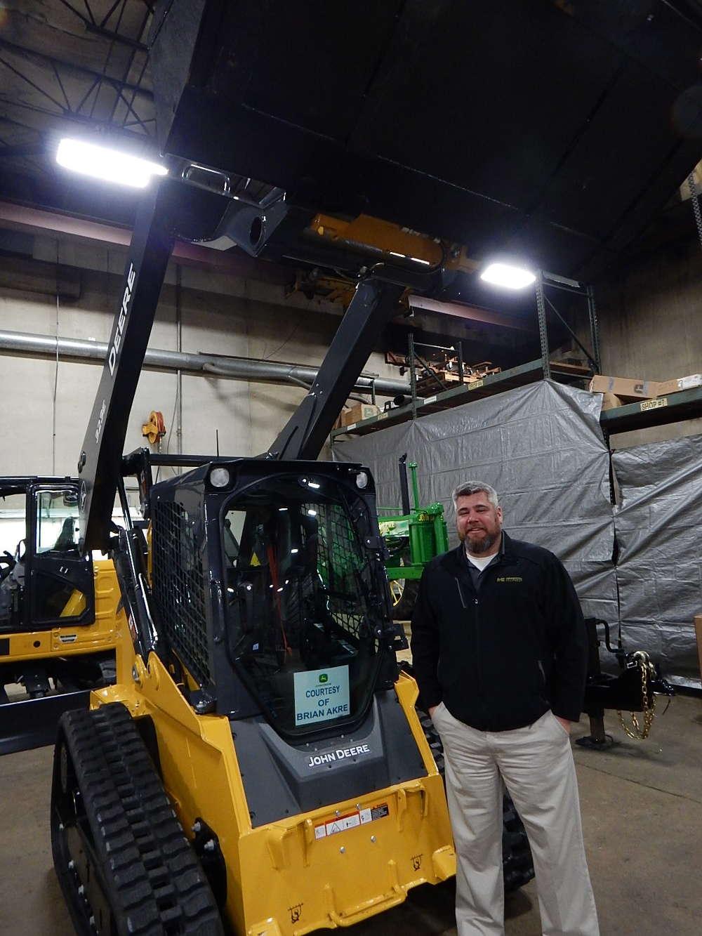 Kevin Knauss, commercial sales of Minnesota  Equipment, Rogers, Minn., stands with a John Deere 323E track machine courtesy of Brian Akre, Zimmerman, Minn.