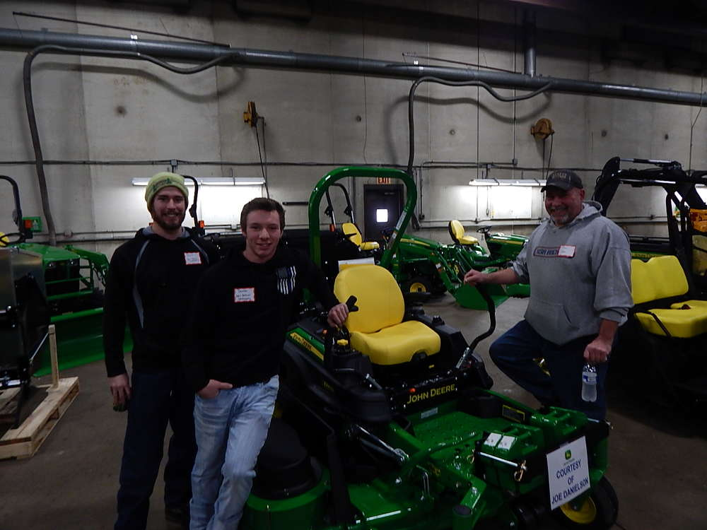 (L-R) David Zachman, operator; Dexter Dehmer, operator and co-owner; and Dan Dehmer, owner, all of Dehmer Landscaping, St. Michael, Minn., take a look at a new John Deere mower.