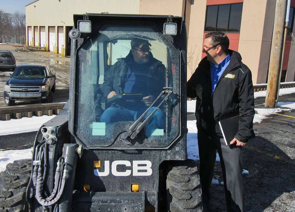 Walsh Equipment's Chad Brocious (R) spoke with Randy Huston of Paint Township, Somerset County, about the dealership's line of JCB equipment at the outdoor equipment display.