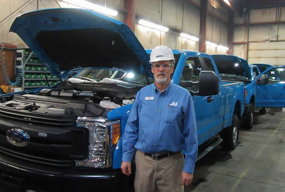 Seen here with a lineup of energy fleet vehicles being prepped for service bodies, J&J Truck Equipment's General Manager David Spear provided insights into the company's manufacturing and fabrication capabilities.