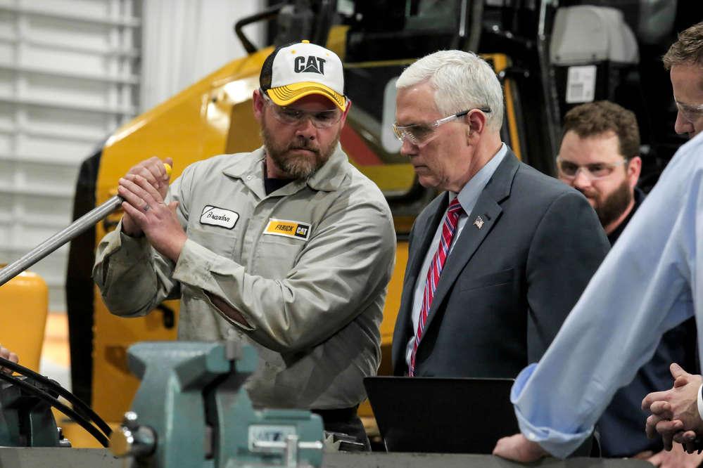 Brandon Goff, Fabick Cat service technician, demonstrates a service process as Vice President Pence looks on.