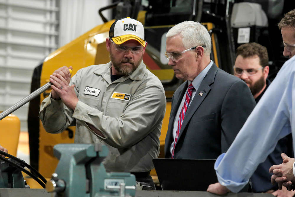 Brandon Goff, Fabick Cat service technician, demonstrates a service process as Vice President Pence looks on.
