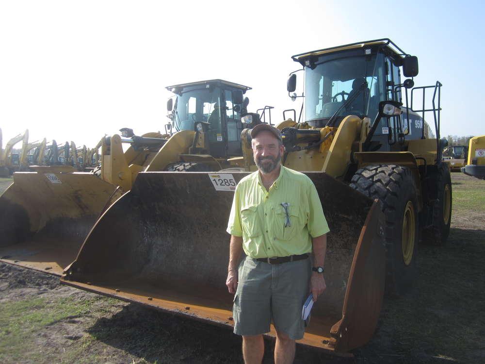 Steve Debaun, president, Track II Corporation, Lakeville, Minn., looks over these two Caterpillar 950K wheel loaders.