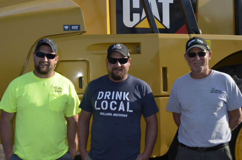 It's February and if you live in Holland, Mich., you jump at the chance to go to Kissimmee, Fla. — a big auction filled with late-model Caterpillars makes that decision even easier. (L-R) are John Brewer of Don Hoe Excavation, and Jason Brewer and Jerry Brewer, both of BS&G Recycling.