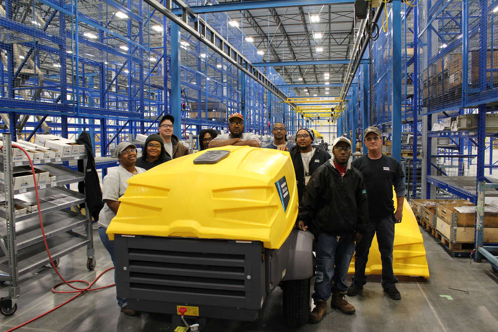 Atlas Copco engineers, product managers and production crew celebrate the first compressor to roll off of the production line at the company's new Rock Hill, South Carolina, plant.
