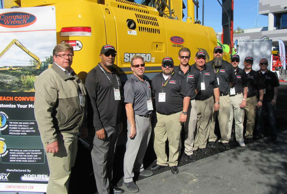 Seen here with CW Machine Works/Company Wrench's Kobelco long reach excavator at the company's outdoor equipment display (L-R) are Alex Samarin, Bernard Whitley, Sean Haviland, Danny Seal, Eric Thornton, Hugh Gordon, Gabe Clark, Billy Wall, Clay Durham and Brad Hutchinson.