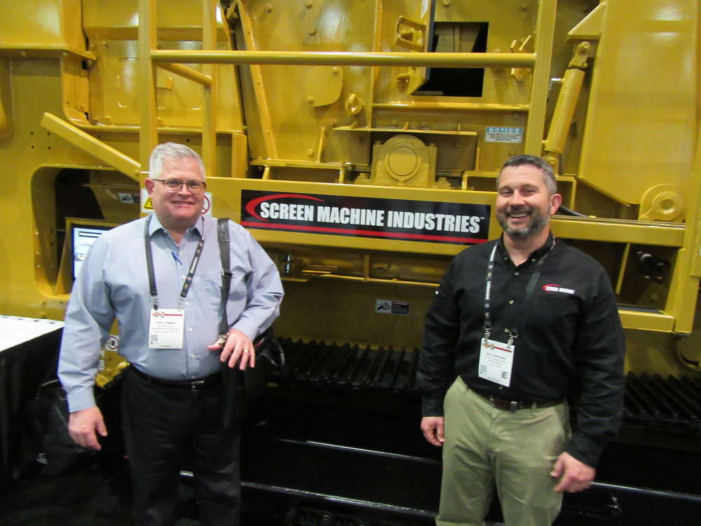 Murrysville Machinery Company's Sam Stimmel (L) stopped by at the Screen Machine Industries equipment display to speak with Rick Brown about the company's latest machine introductions.